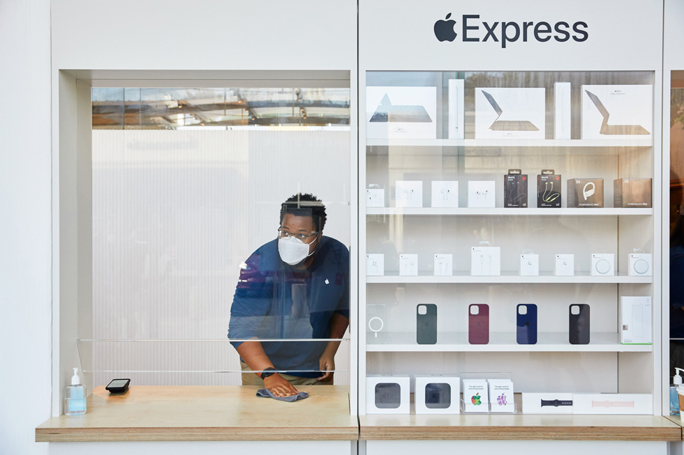 An Apple employee wipes down a window station at the Express storefront at Apple Highland Village.
