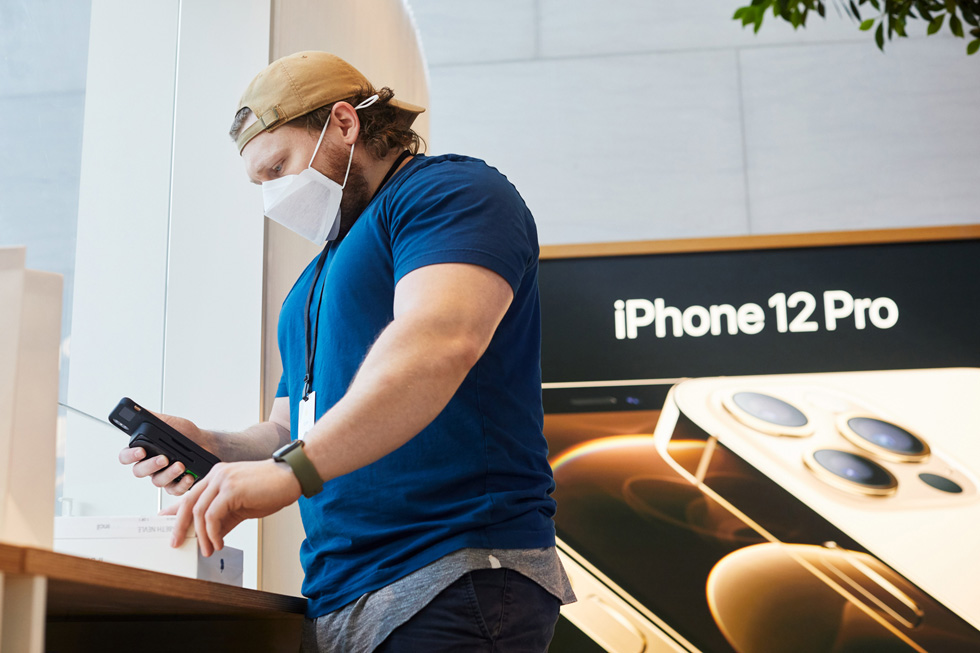 An Apple employee scans Apple products at Apple Highland Village.