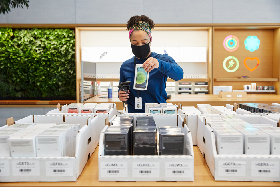 An Apple employee stocks the latest Apple products at Apple Highland Village.
