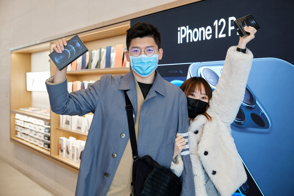 Customers at Apple Sanlitun show off their new iPhone 12 Pro Max purchases.