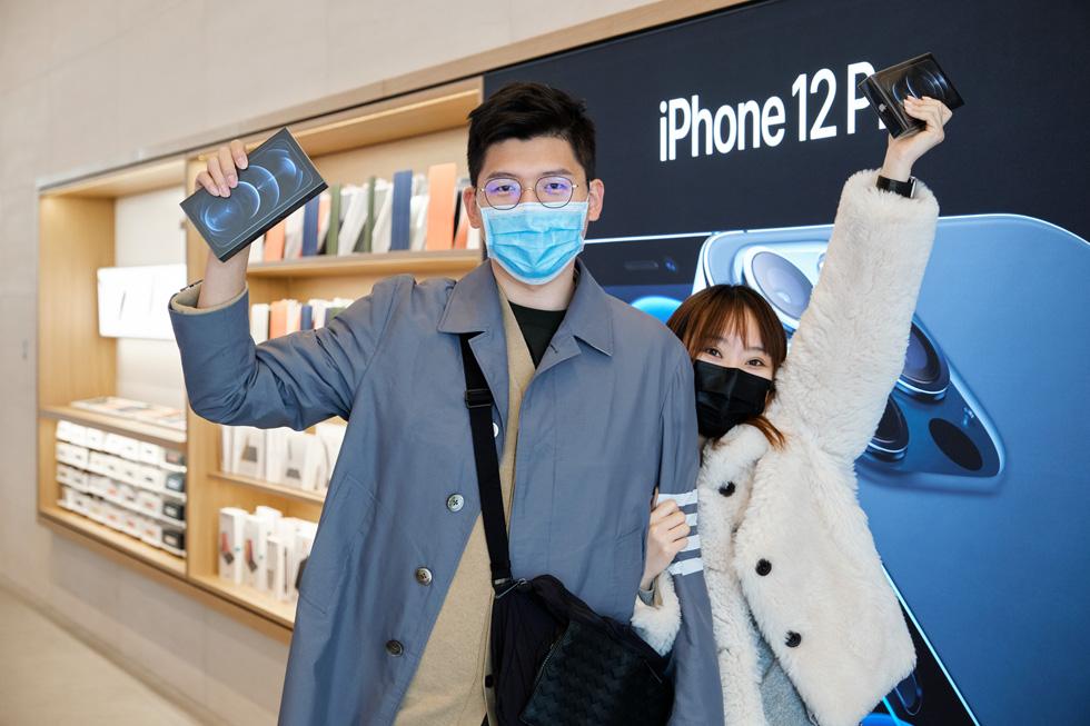 Un client et une cliente d'Apple Sanlitun brandissent fièrement leurs nouveaux iPhone 12 ProMax qu'ils viennent juste d'acquérir.