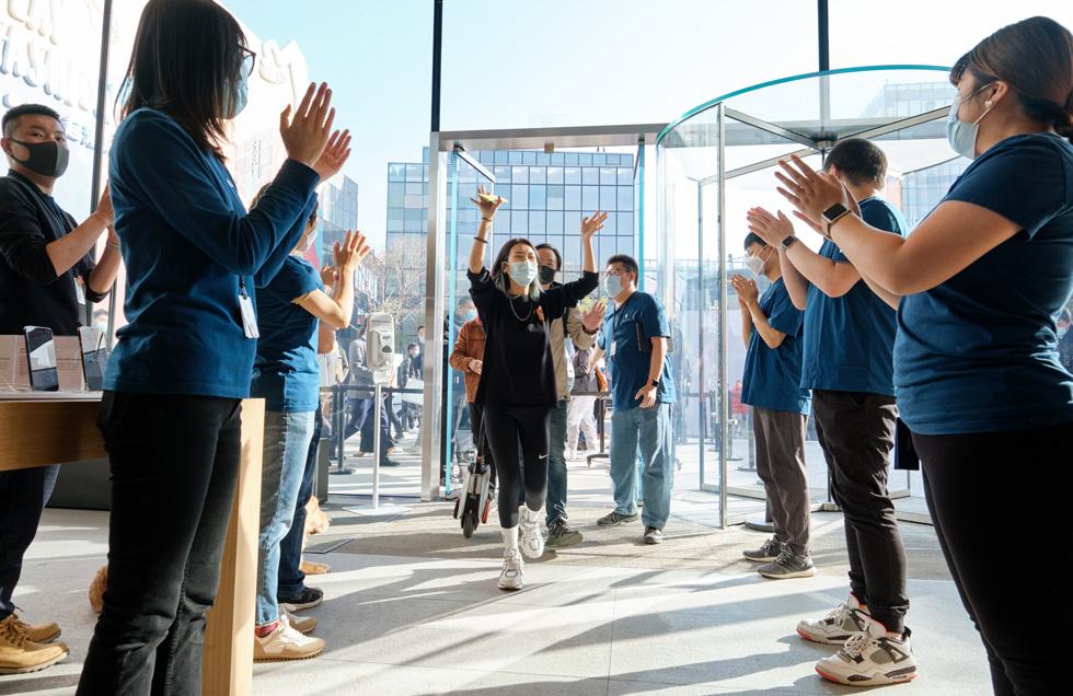 À Apple Sanlitun, des membres de l'équipe accueillent des clients venus découvrir les iPhone 12 ProMax et iPhone 12mini désormais présentés en magasin.