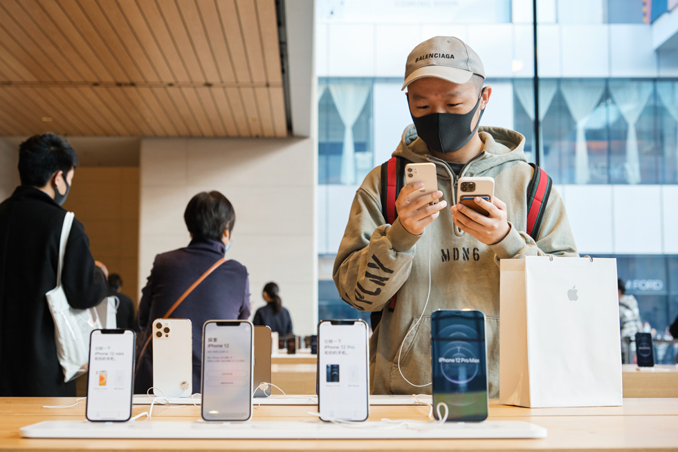 A customer at Apple Sanlitun closely examines iPhone 12 mini.