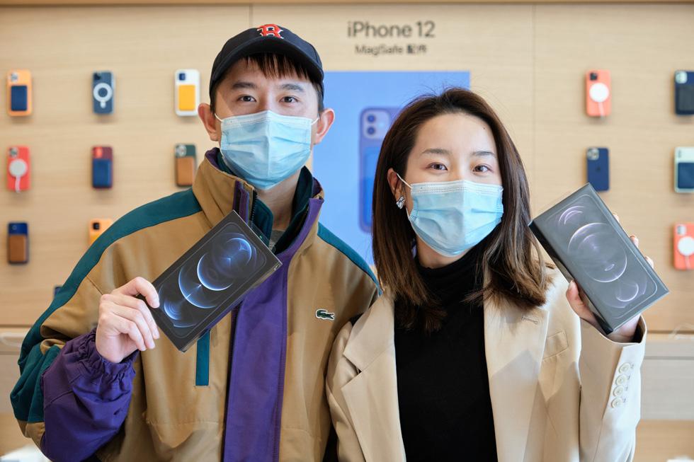 Un client et une cliente d'Apple Sanlitun tenant leurs nouveaux iPhone 12 ProMax qu'ils viennent juste d'acquérir.