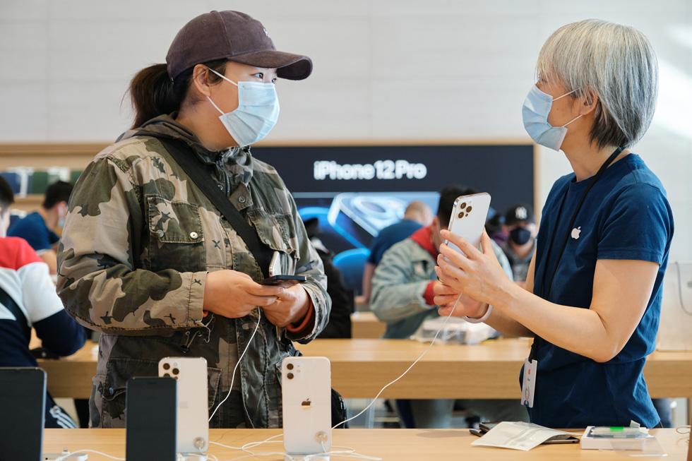 Une membre de l'équipe d'Apple Sanlitun répond aux questions d'une cliente au sujet de l'iPhone 12 ProMax.
