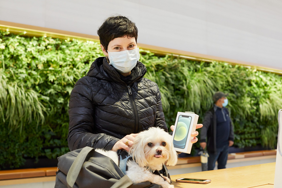 A customer and her dog holding her new iPhone 12 mini.