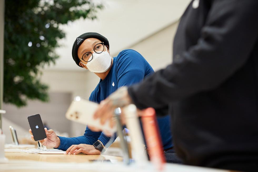 Un membre de l'équipe d'Apple FifthAvenue montre un iPhone 12mini à un client.