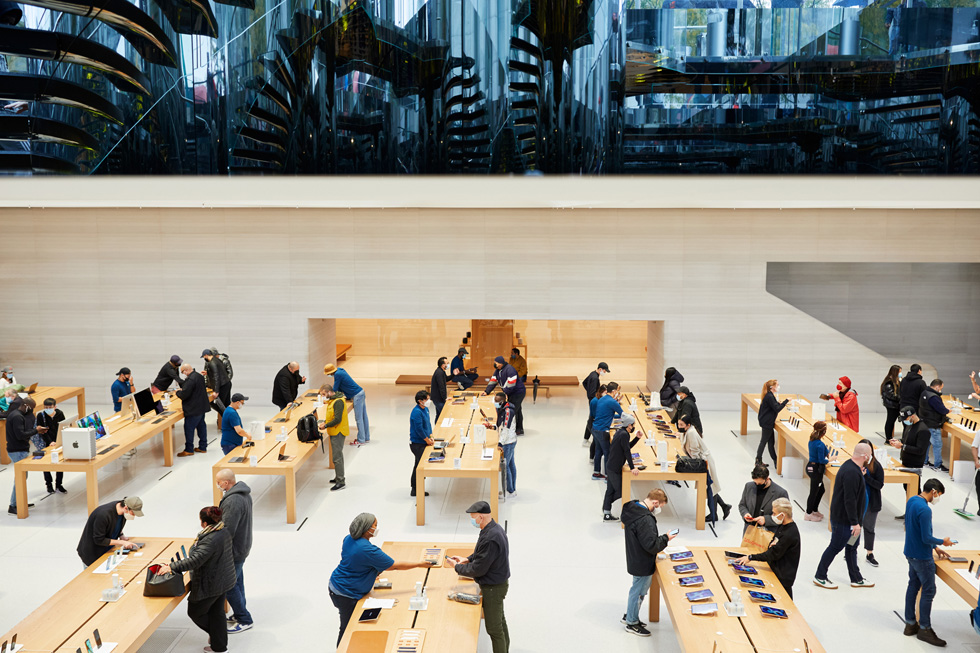 Des clients et des membres de l'équipe Apple aux différentes tables de présentation d'Apple FifthAvenue.