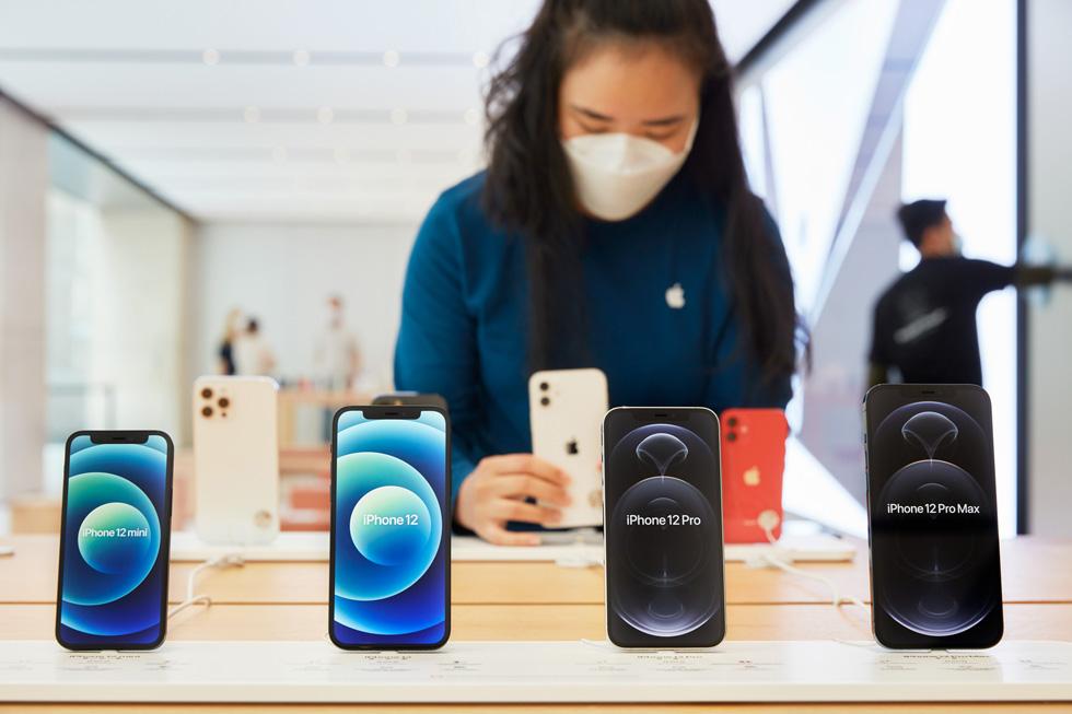 Une membre de l'équipe d'Apple Sydney ajuste la présentation des iPhone 12mini, iPhone 12, iPhone 12Pro et iPhone 12 ProMax.