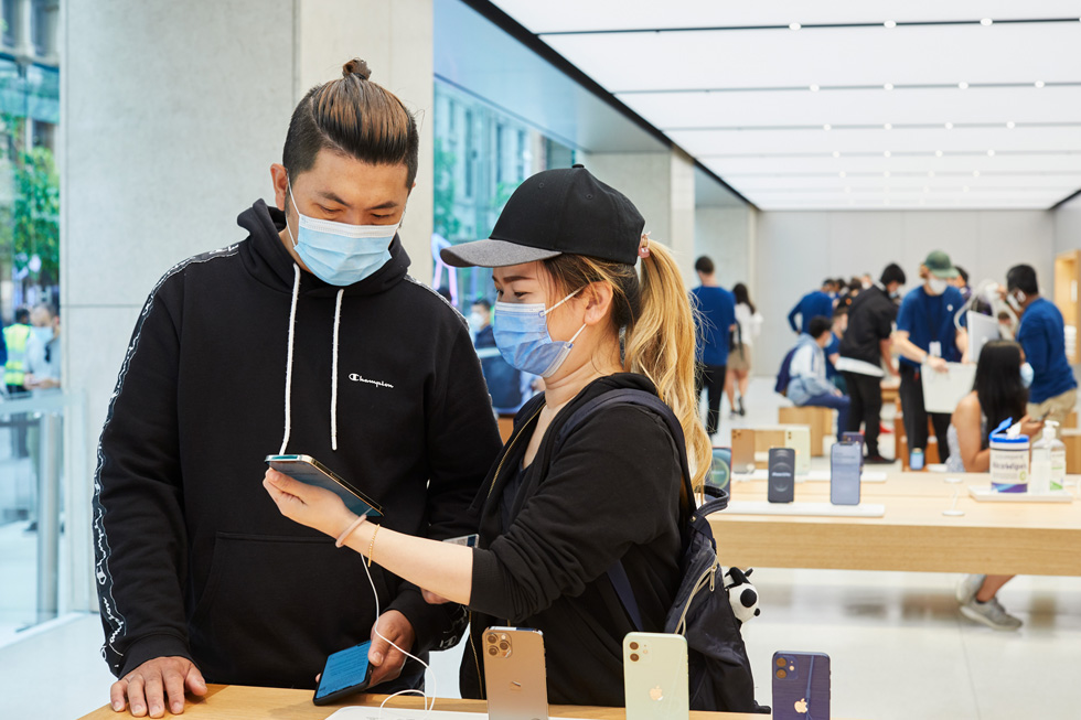 Des clients d'Apple Sydney manipulent le nouvel iPhone 12 ProMax à l'une des tables de présentation.