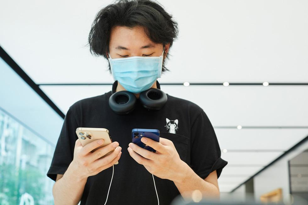 Un client d'Apple Sydney compare l'iPhone 12 ProMax à l'iPhone 12mini.
