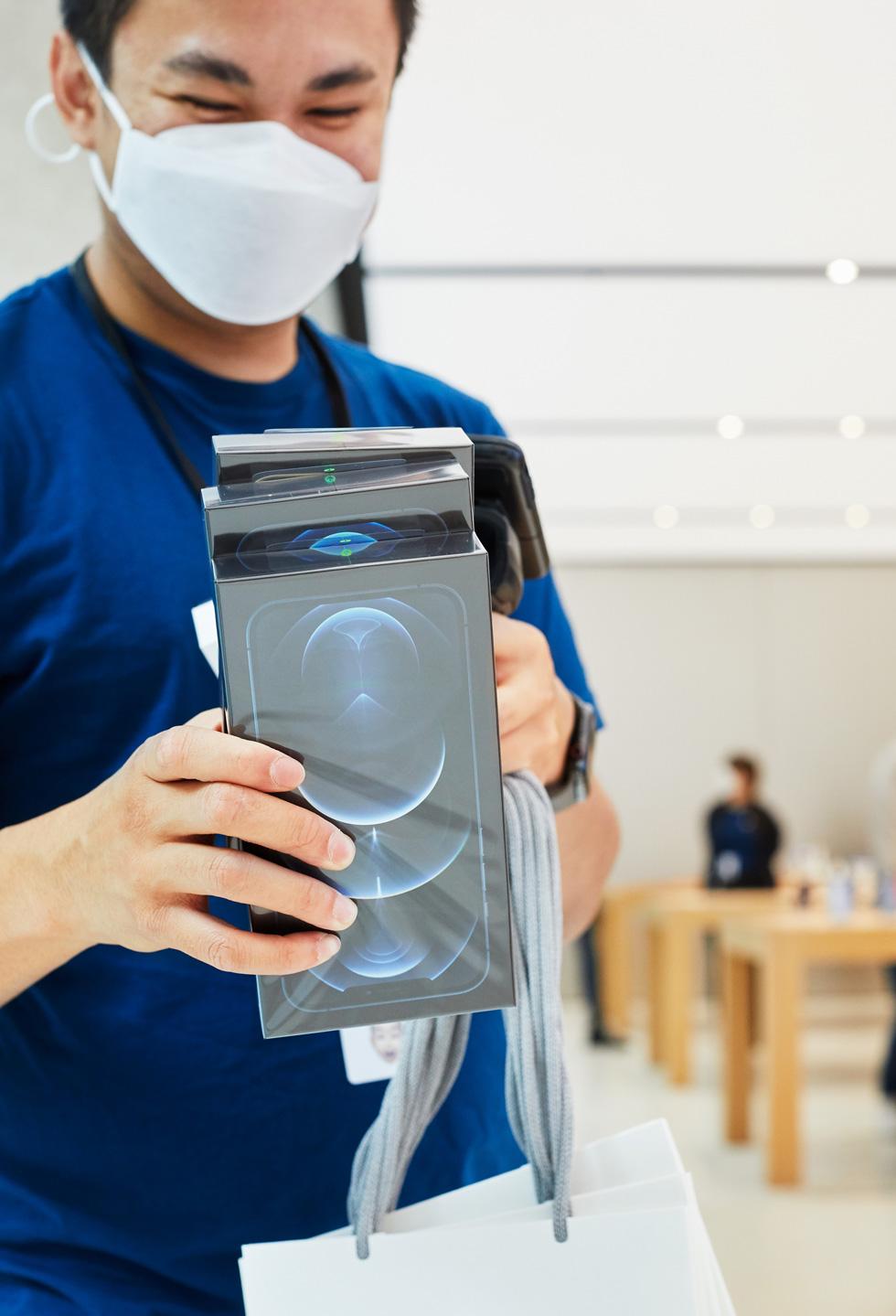 Un membre de l'équipe d'Apple Sydney scanne des coffrets d'iPhone 12 ProMax.