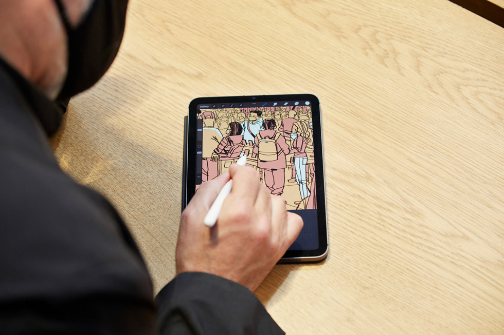 Artist Jorge Colombo using an Apple Pencil to draw the action inside Apple Fifth Avenue on the new iPad mini.