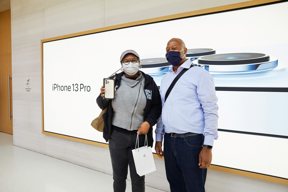 An Apple Fifth Avenue customer showing off her iPhone 13 Pro purchase with her friend.