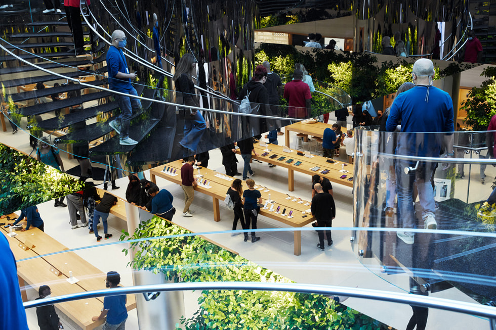 Staircases looking down into Apple Fifth Avenue's display tables with customers and team members all around.