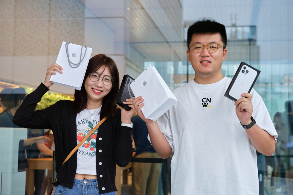 Two customers celebrating their iPhone 13 purchases.