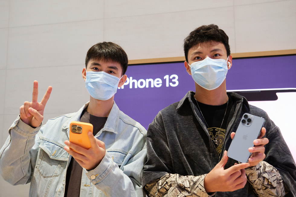 A customer with a friend, holding the new Sierra Blue iPhone 13 Pro at Apple Sanlitun.