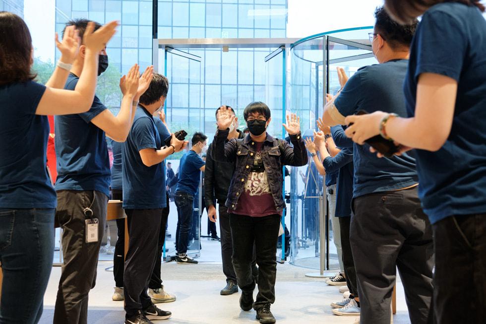 Team members at Apple Sanlitun greet customers arriving for the iPhone 13 lineup.