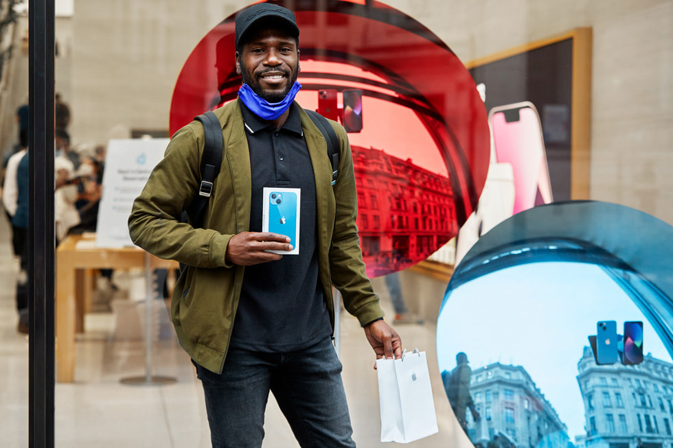 An Apple Regent Street customer showing off his new iPhone 13 purchase.