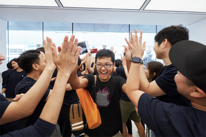 En kunde får high fives af Apple Kyoto's ansatte