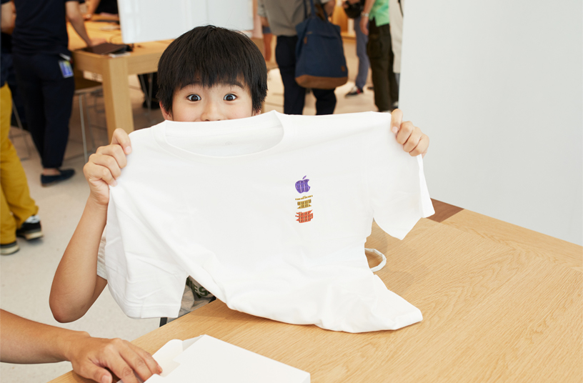 Kunde i Apple Kyoto holder en t-shirt op.