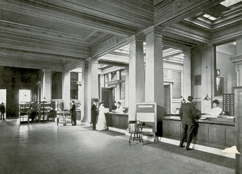 Archival photo of patrons at the library's circulation desk.