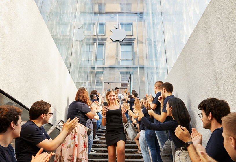 Customers descend the stairs of the glass fountain entrance to Apple Piazza Liberty.