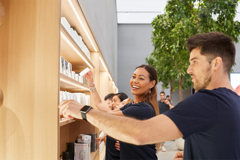 Apple Piazza Liberty team members stocking shelves in the store.