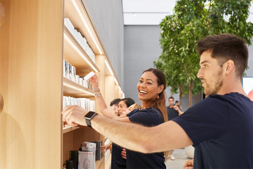 I membri del team di Apple Piazza Liberty calzano gli scaffali nel negozio.