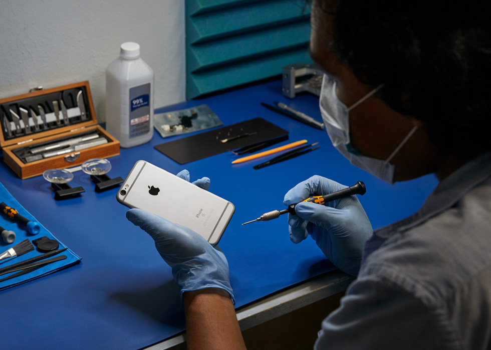 A repair technician performs a repair on an iPhone.