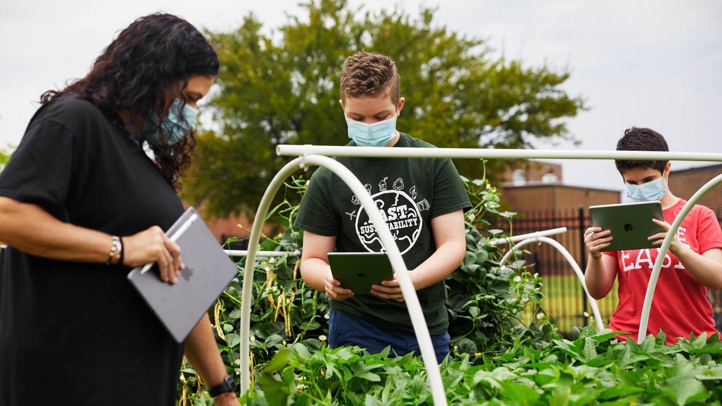 Jodie Deinhammer, Stayton Slaughter, and Annabeth Hook working in Coppell Middle School East's community garden.