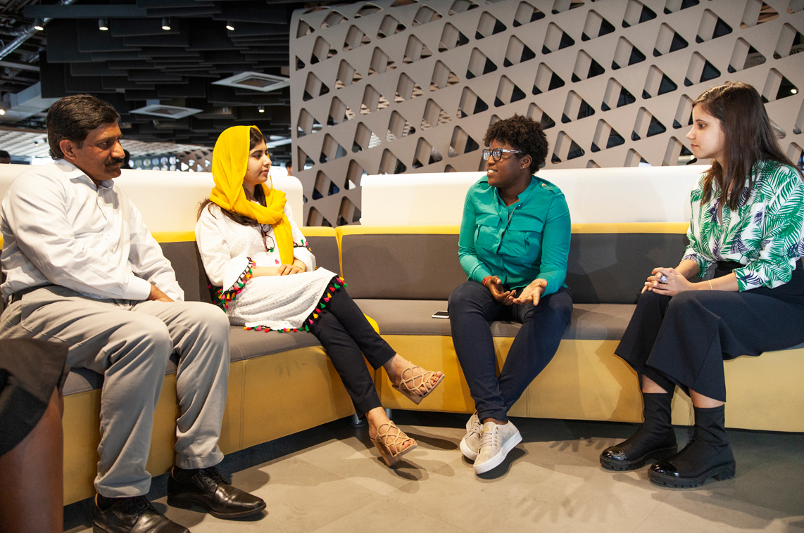 Malala Yousafzai sits with three people on a couch at the Apple Developer Academy in Rio.