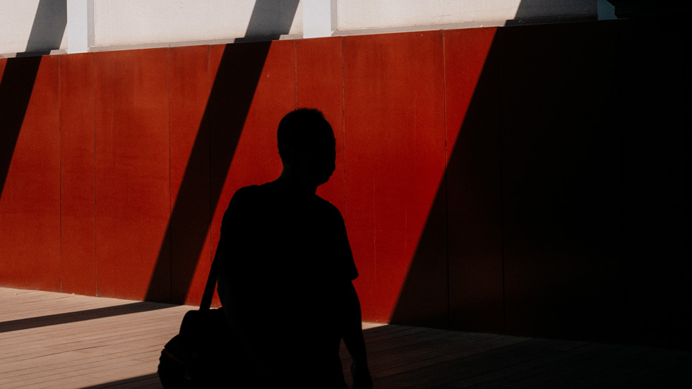 A silhouette of Eric Zhang in front of a red wall.