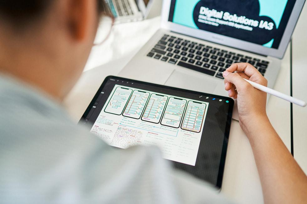 Usando un iPad, un Apple Pencil y una MacBook Air, un estudiante trabaja en el desarrollo de una app.