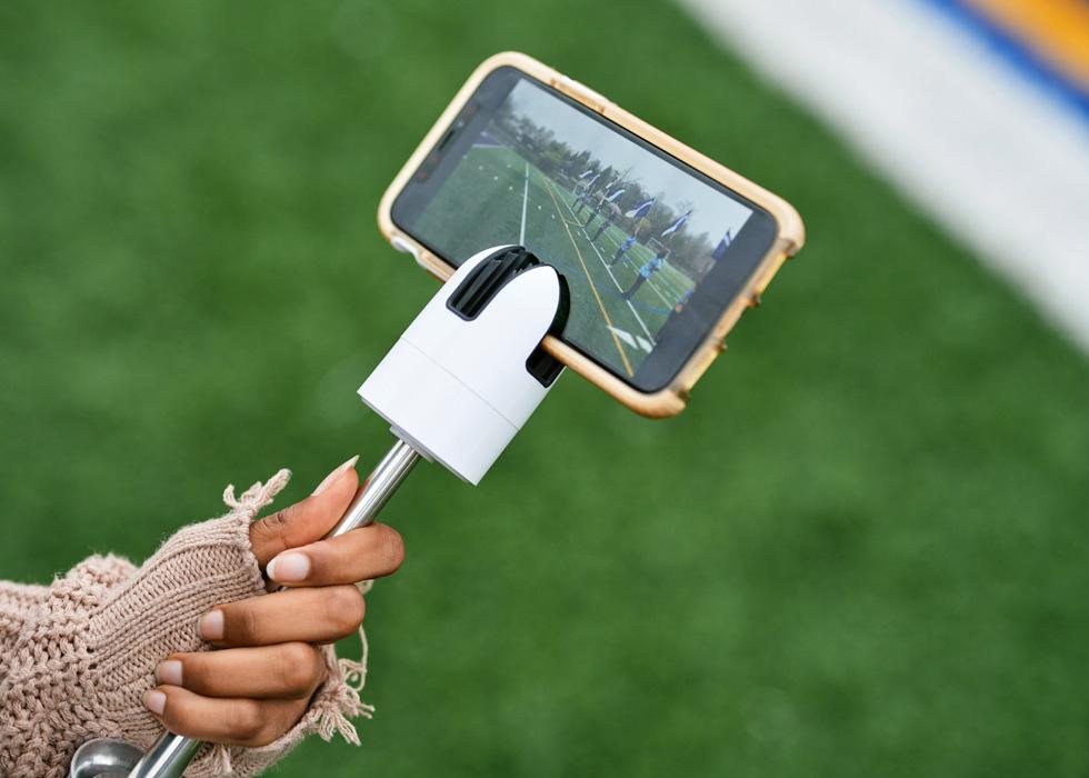 Eine Schülerin der New Rochelle High School verwendet ein iPad, um Videos von Fahnenträger:innen auf dem Sportplatz aufzunehmen.