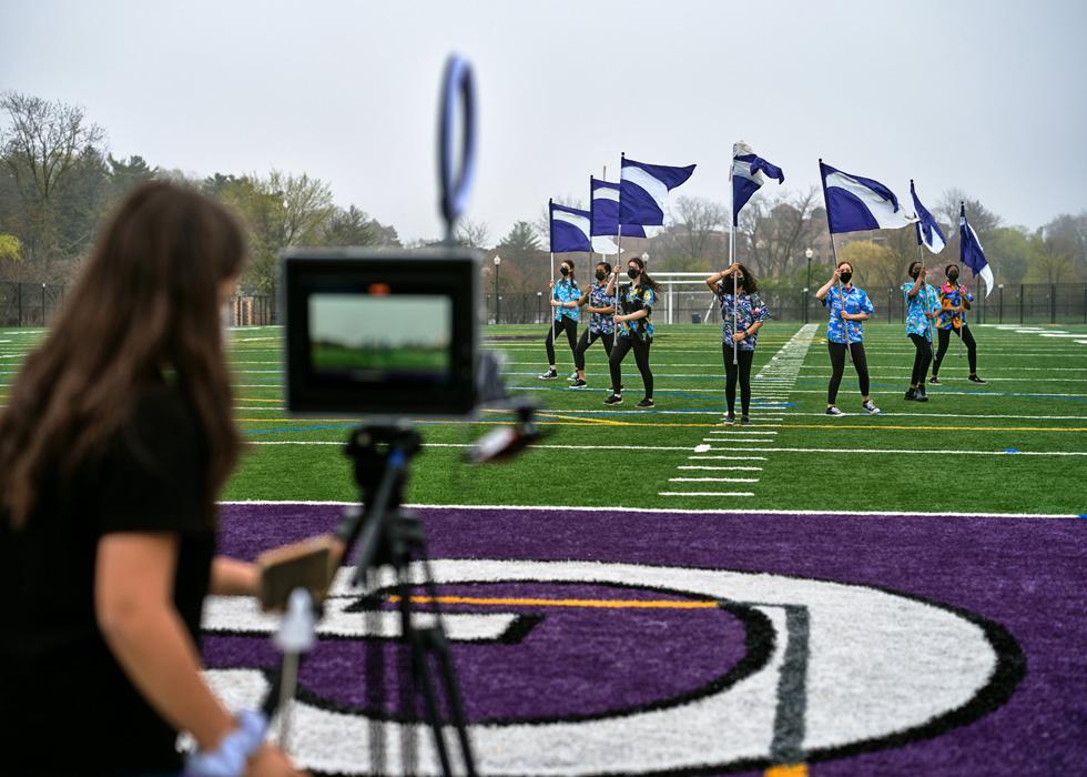 Eine Schülerin der New Rochelle High School verwendet ein iPad, um Mitschüler:innen mit Flaggen auf dem Sportplatz aufzunehmen.