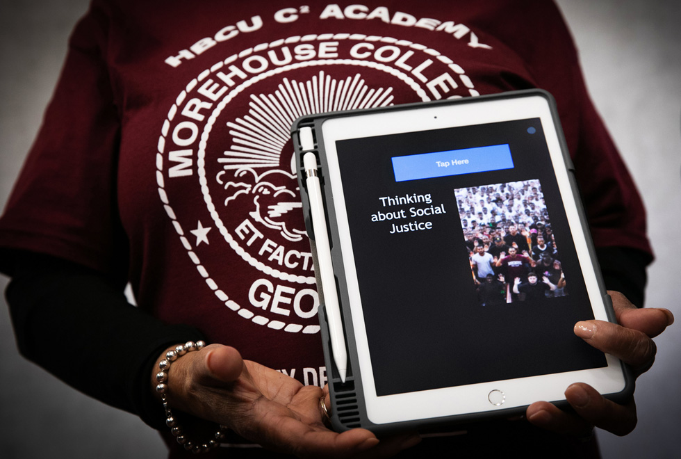 """A person wearing an HBCU C2 Morehouse College sweatshirt holds an iPad Pro with the words """"Thinking about social justice"""" displayed onscreen."""