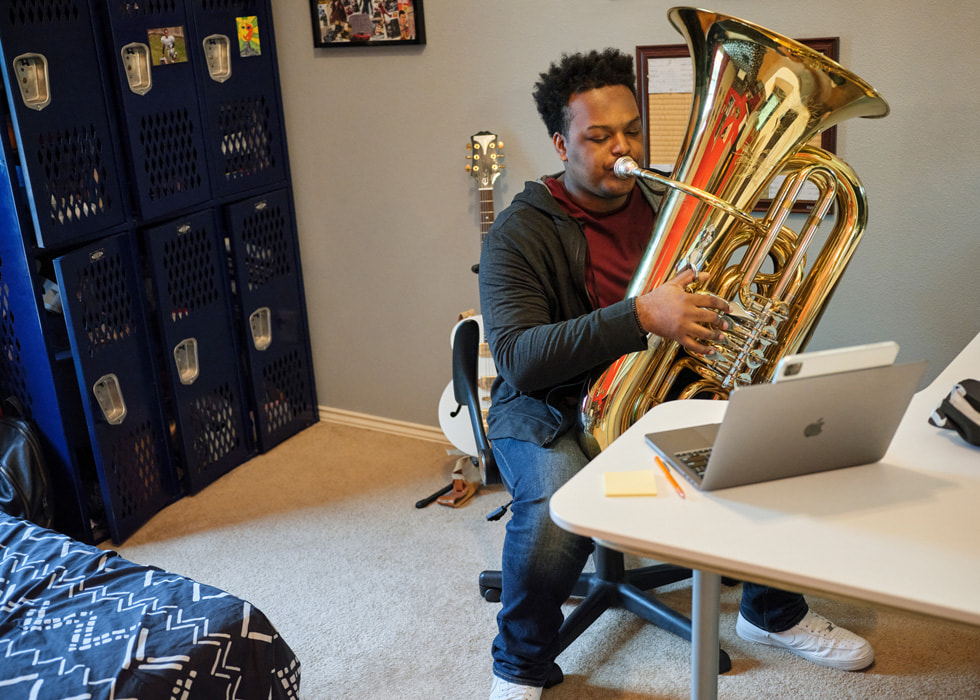 A man practices the tuba in front of an open MacBook Pro.