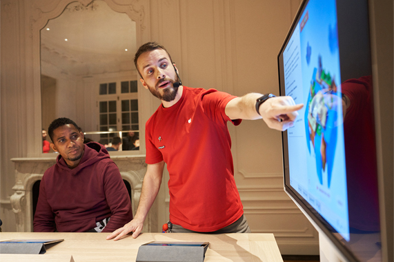 An Apple team member showing a customer a demo.
