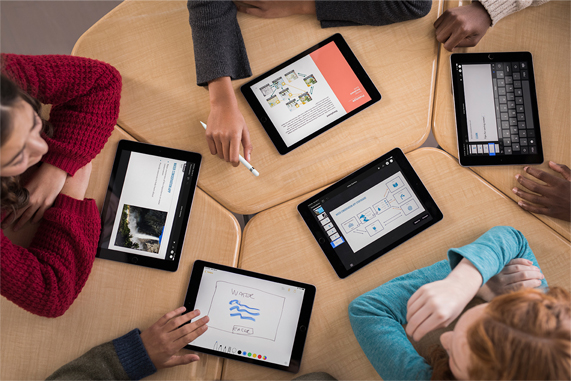 A table of young students using iPads.
