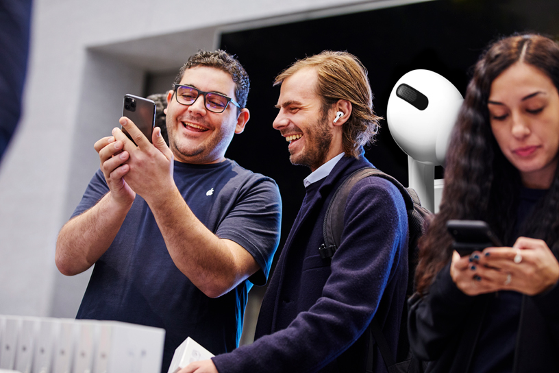 An Apple Piazza Liberty team member helps a customer set up AirPods Pro.