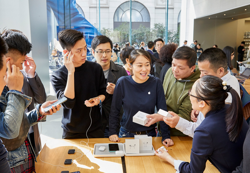 Customers around a table at Apple Nanjing East in Shanghai.