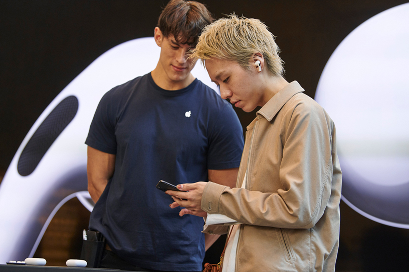 An Apple team member watches a customer try out AirPods Pro.