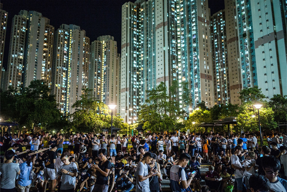 A mass of people playing Pokémon Go in a park at night in Hong Kong.