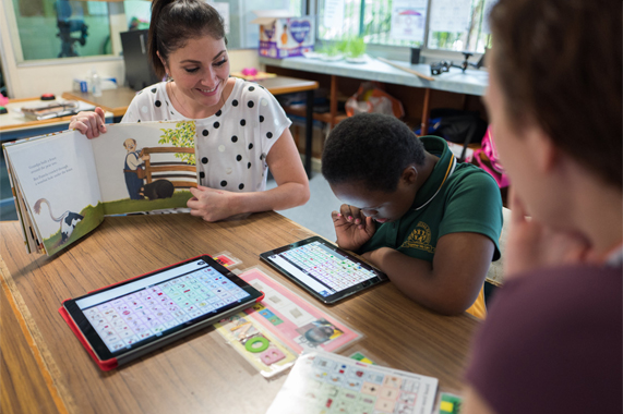 Teacher working with a student using an iPad.