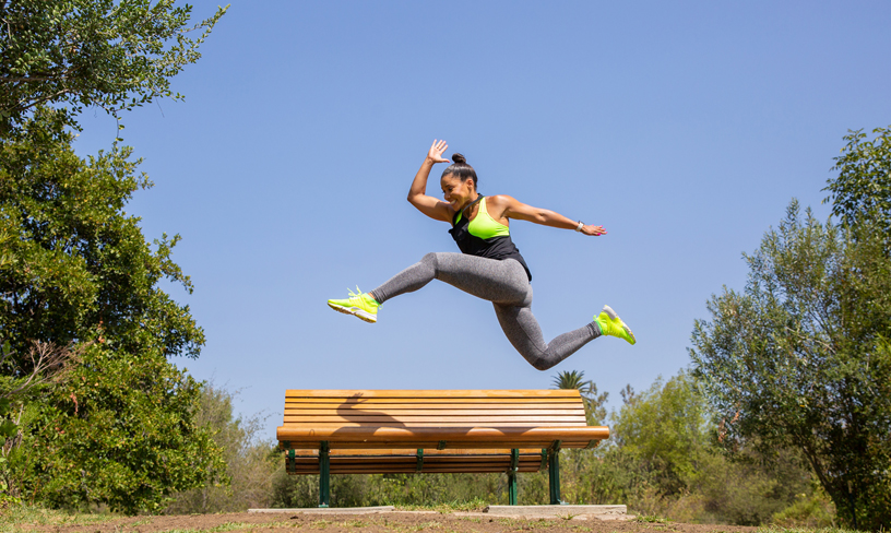 Celebrity fitness trainer Jeanette Jenkins jumping over a bench.