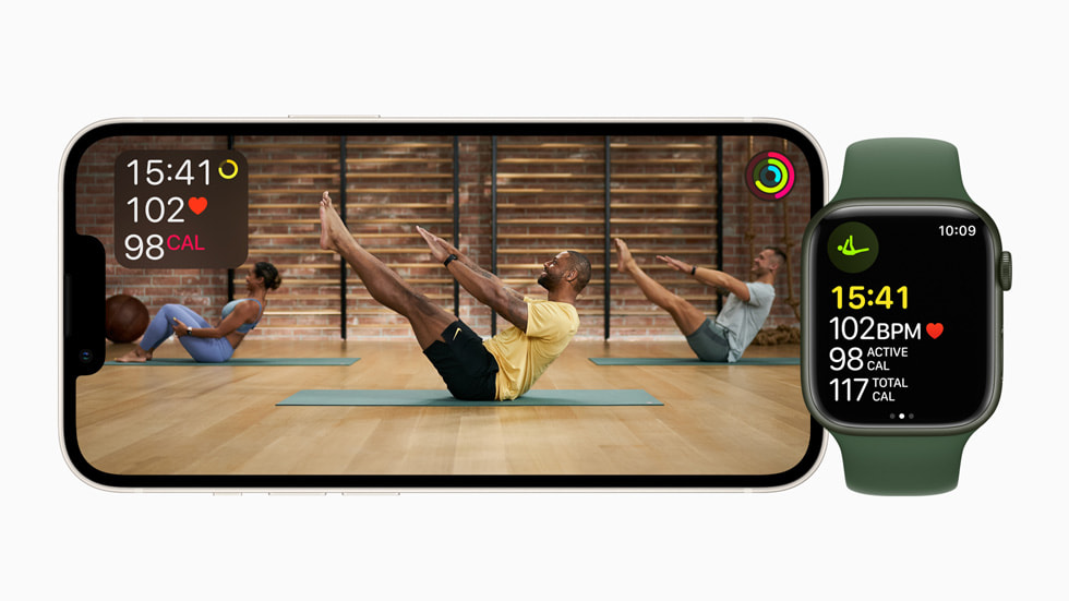 A horizontal iPhone screen shows a Fitness+ Pilates session alongside Apple Watch Series 7.