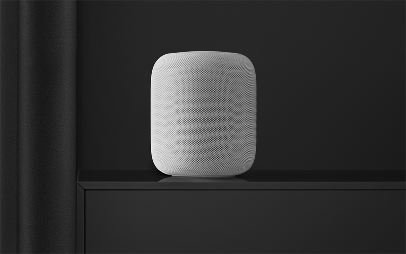 White HomePod speaker on a black shelf.