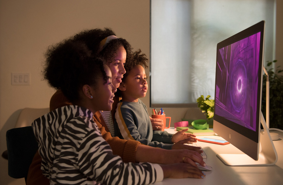"""Una donna utilizza il mouse con un iMac 27"""" mentre due bambini guardano lo schermo."""