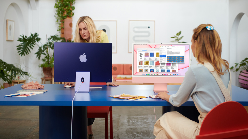 Two women use their iMac in a co-working space.